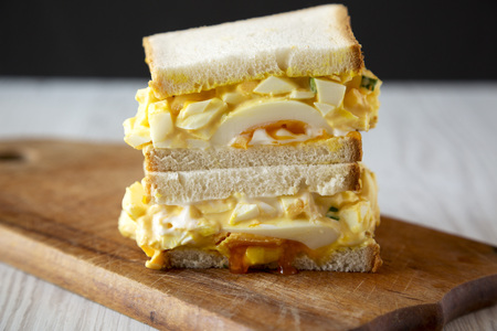 Homemade egg salad sandwich for breakfast on a rustic wooden board, side view. Close-up. Stockfoto