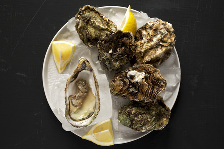 Fresh oysters on a plate over black surface, view from above. Overhead, flat lay, top view. Close-up.