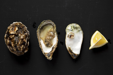 Fresh oysters on a black background. Flat lay, from above, overhead.