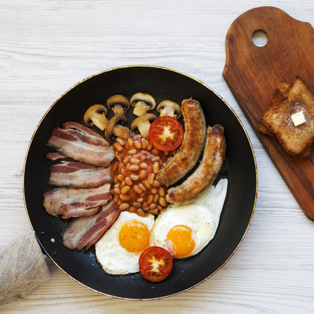 English breakfast in a pan with fried eggs, bacon, beans, sausages and toasts on a white wooden surface, top view. From above, overhead.
