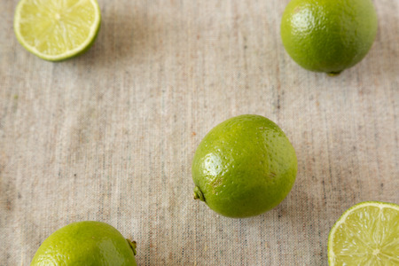 Whole and cut green citrus limes on cloth, low angle view.