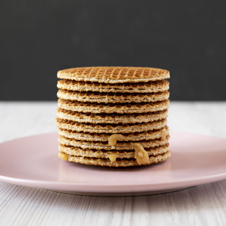 Stack of homemade Dutch stroopwafels with honey-caramel filling on a pink plate, side view. Close-up.