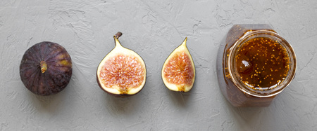 Fig jam in glass jar and fresh figs over concrete background, top view. Flat lay, from above, overhead. Reklamní fotografie