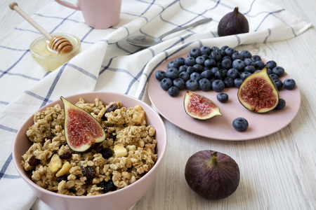 Pink bowl of fruit granola with fruits and honey, low angle view. Close-up. Imagens