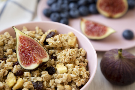Pink bowl of fruit granola with fruits, low angle view. Close-up.