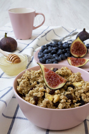 Fruit granola with fruits in a pink bowl ready to eat, side view. Closeup. Imagens