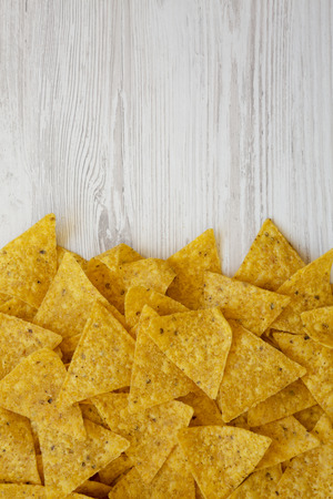 Tortilla chips on a white wooden background, top view. Mexican food. Flat lay, overhead. Copy space.