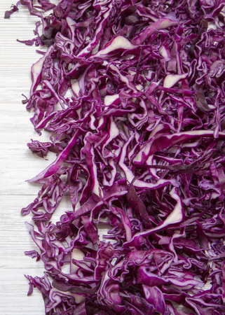 Chopped red cabbage on a white wooden background, close-up. Top view, from above, overhead.