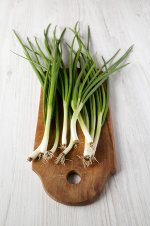 Fresh green onions on a rustic wooden board over white wooden background, side view. Banco de Imagens - 122686819