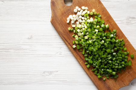 Chopped green onions on a rustic wooden board on a white wooden background, top view. Overhead, flat lay, from above. Copy space.