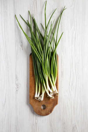 Fresh green onions on a cutting board on a white wooden background, top view. From above, overhead, flat lay. Banco de Imagens - 122688470