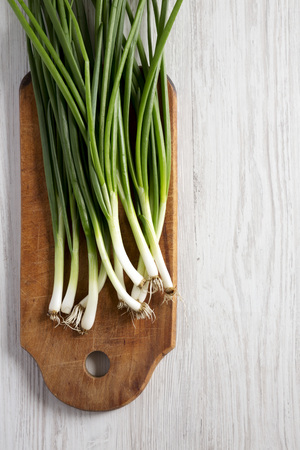 Fresh green onions on a cutting board on a white wooden table, top view. From above, overhead, flat lay. Copy space. Banco de Imagens - 122688472