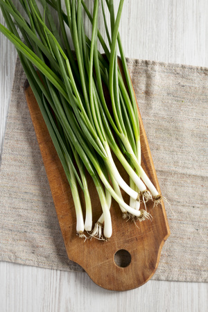 Fresh green onions on a cutting board on a white wooden background, top view. From above, overhead, flat lay. Close-up.