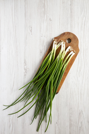Fresh green onions on a cutting board on a white wooden background, overhead view. From above, top view, flat lay. Copy space.