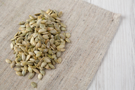 Roasted pumpkin seeds on cloth over white wooden background, low angle view. Copy space.