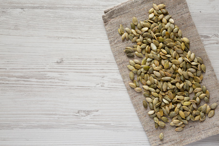 Roasted pumpkin seeds on a white wooden table, top view. Flat lay, overhead, from above. Copy space.