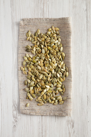 Roasted pumpkin seeds on a white wooden background, top view. Flat lay, overhead, from above. Foto de archivo