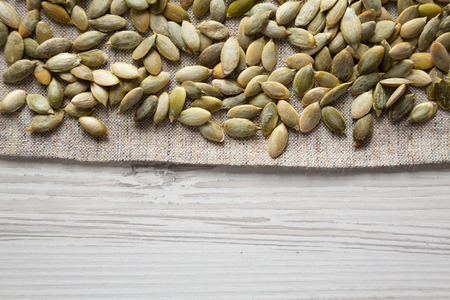 Roasted pumpkin seeds on cloth over white wooden background, top view. Flat lay, overhead, from above. Copy space. Foto de archivo