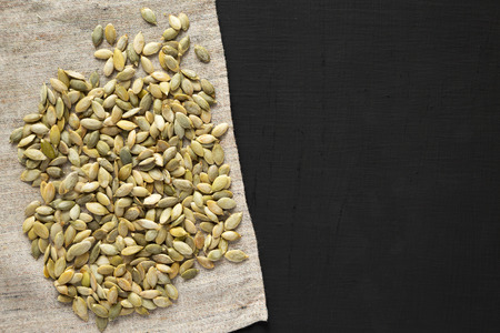 Roasted pumpkin seeds on a black background, top view. Flat lay, overhead, from above. Copy space.