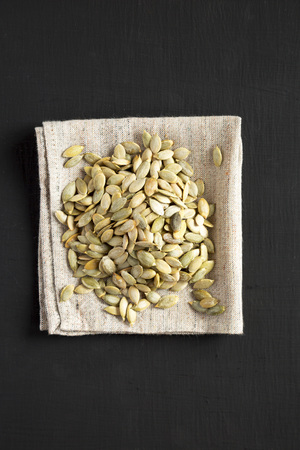 Roasted pumpkin seeds on a black surface, top view. Flat lay, overhead, from above. Foto de archivo