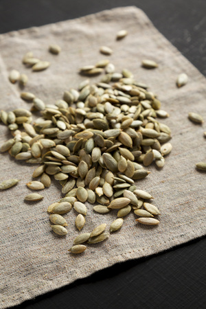 Roasted pumpkin seeds on cloth, side view. Close-up.