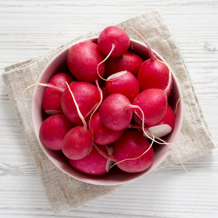 Fresh red radishes in a pink bowl over white wooden surface, top view. Flat lay, overhead, from above.