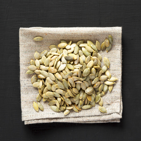 Roasted pumpkin seeds on a black background, top view. Flat lay, overhead, from above. Close-up.