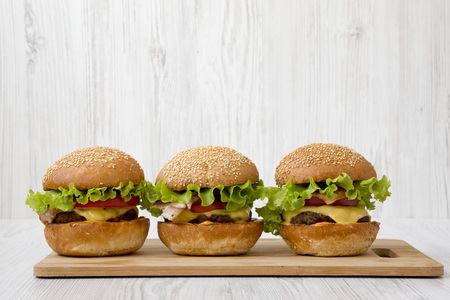 Homemade cheeseburgers on a bamboo board, side view. Close-up. Imagens