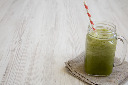 Glass jar mug filled with green celery smoothie, side view. Copy space.
