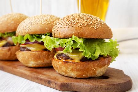 Cheeseburger fatti in casa e bicchiere di birra fredda, vista laterale. Avvicinamento. Messa a fuoco selettiva.
