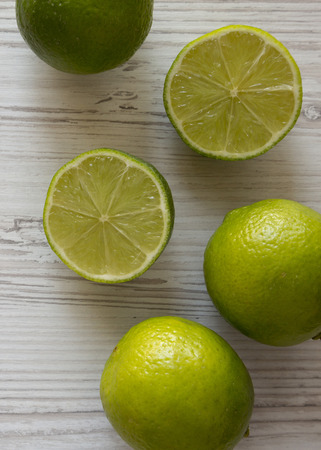 Green citrus limes on a white wooden background, top view. From above, overhead, flat lay. Close-up. 免版税图像