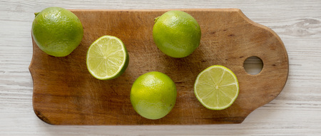 Whole and cut green citrus limes on a rustic wooden board over white wooden background, top view.