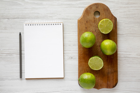 Whole and cut green citrus limes on a rustic wooden board, notepad with pencil over white wooden surface, top view.