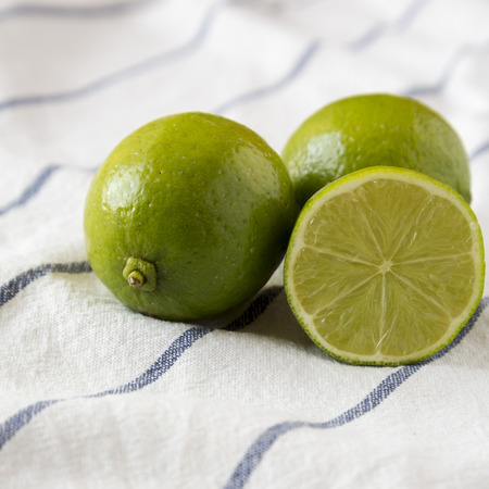 Whole and cut green citrus limes on cloth, side view. Close-up.
