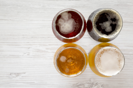 Craft beer assortment on a white wooden table, top view. Overhead, from above, flat lay. Copy space.