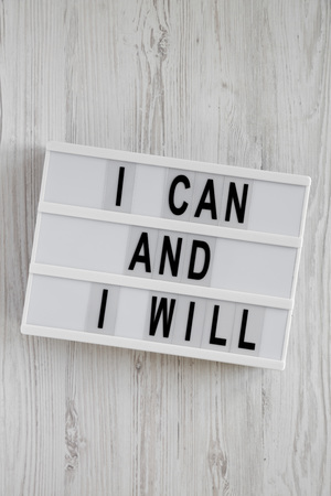 Modern board with 'I can and I will' words on a white wooden background, top view. Overhead, from above. Flat lay. Imagens