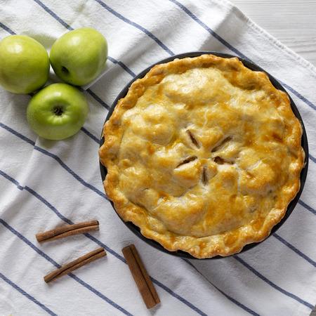 Torta di mele fatta in casa su stoffa, vista dall'alto. Disteso piatto, sopra la testa, dall'alto. Avvicinamento.