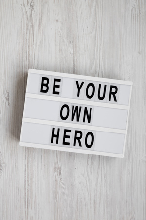 'Be your own hero' words on a modern board over white wooden surface, top view. Flat lay, overhead, from above. 写真素材