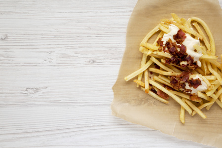 Fastfood: french fries with cheese sauce and bacon on a white wooden background, top view. Flat lay, from above, overhead. Copy space. 版權商用圖片