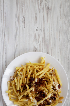 Tasty fast food: french fries with cheese sauce and bacon on a white plate over white wooden background, top view. Flat lay, from above, overhead. Copy space.