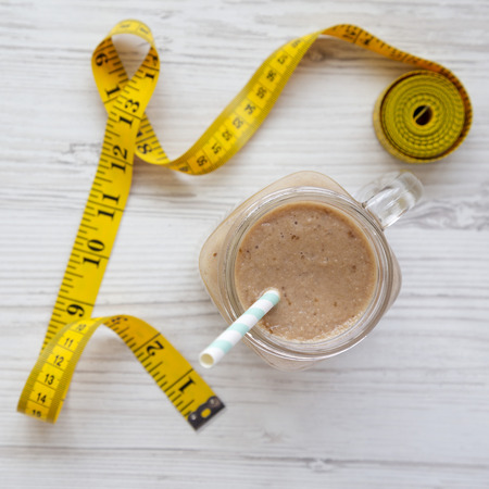 Banana apple smoothie in a glass jar, measuring tape on a white wooden surface, view from above. Flat lay, top view, overhead. Dieting concept.