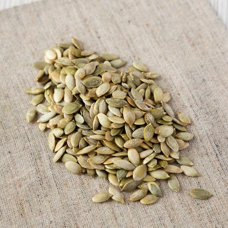 Roasted pumpkin seeds on cloth, low angle view. Closeup.