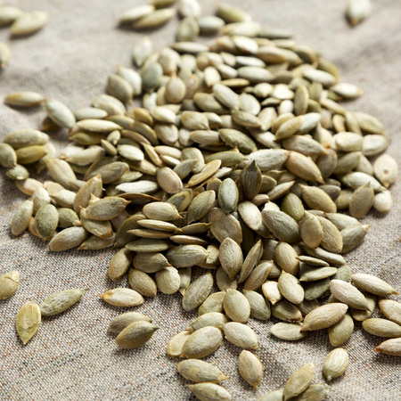 Roasted pumpkin seeds on cloth, low angle view. Close-up.