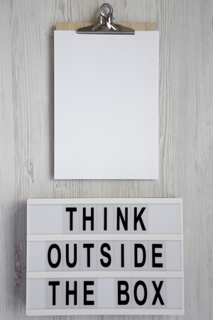 'Think outside the box' words on a lightbox, clipboard with blank sheet of paper on a white wooden surface, top view. Flat lay, overhead, from above. Copy space.