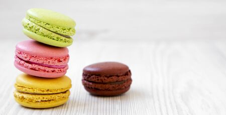 Sweet and colorful macarons on a white wooden surface, side view. Copy space.