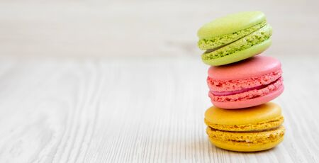 Stack of colorful macarons on a white wooden surface, side view. Space for text.