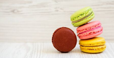 Sweet and colorful macarons on a white wooden background, side view. Copy space.