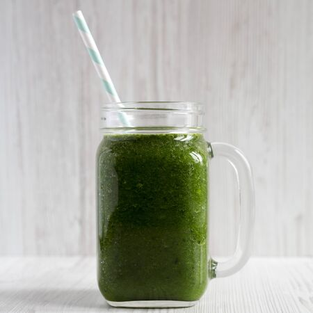 Green smoothie with avocado, spinach and banana in a glass jar over white wooden background, side view. Close-up.