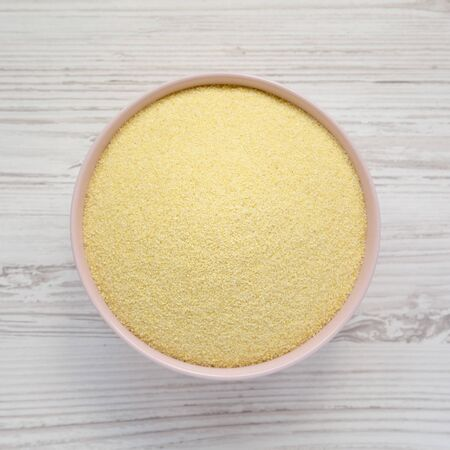 Top view, dry semolina durum flour in a pink bowl over white wooden surface. Overhead, from above, flat lay.