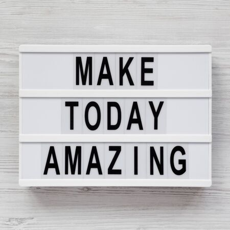 'Make today amazing' words on a modern board on a white wooden surface. From above, overhead, flat lay, top view. Closeup.
